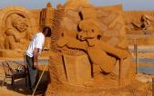 "Sand carver Shanin works on a sculpture during the Sand Sculpture Festival ""Disney Sand Magic"" in Ostend"
